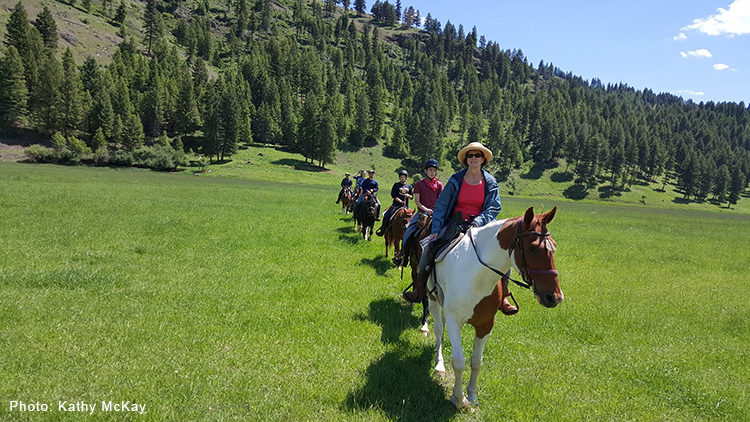 Line of horseback riders at K-Diamond-K Guest Ranch.