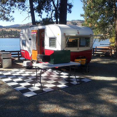 Red and white travel trailer at Fisherman's Cove's RV site.