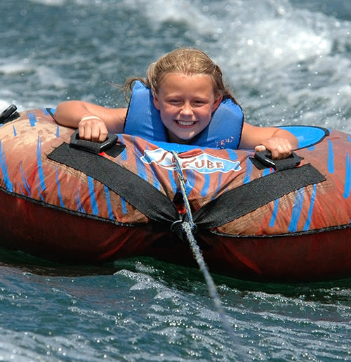 Young girl riding inner tube on water.