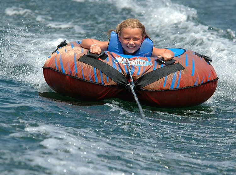 Young girl riding inner tube across water.