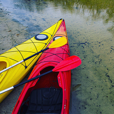 The noses of two kayaks touching. One red and the other yellow.