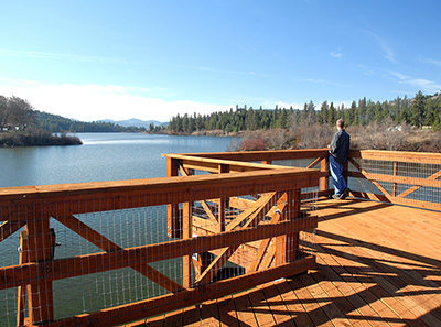 Man viewing Curlew Lake from the rail trail trestle.