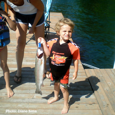 Youngster proudly displays his catch of a rainbow trout.