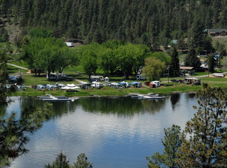 View across lake of Black Beach Resort's grassy RV sites.