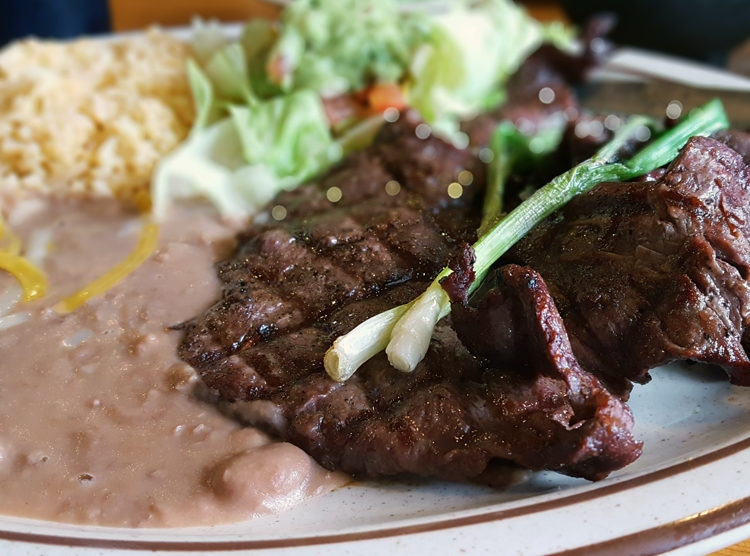 Esther\'s carne asada platter, with steak, beans, rice, guacamole, grilled green onion, and tortillas.